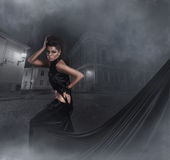 Fashion shoot of a young woman in a dark dress Royalty Free Stock Photography