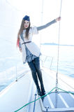 Fashion shoot of a young woman in a sailor costume. Fashion shoot of a young and attractive woman in a sailor costume posing on a boat. The image is taken during Stock Photography