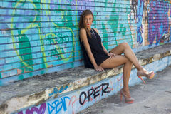Fashion shooting. Girl next to a graffiti wall Royalty Free Stock Photography