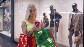 Fashion shopping, attractive girl uses smartphone for shopping in online store during walk through mall in season of. Discounts and sales on black Friday stock footage