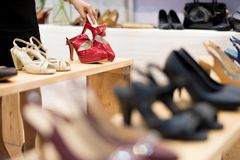Fashion shopping footwear store. Display Shelf in Shoe shop. Shopping in the fashion footwear store and Hand of woman holding a red high heels shoe. trying to stock image