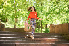 Fashion Shopping Girl Portrait. Beauty Woman with Shopping Bag going home from mall stepping down on stairs outdoors Royalty Free Stock Photos