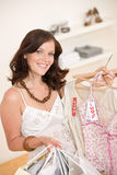 Fashion shopping - Happy woman choose sale clothes. Holding shopping bag Stock Image