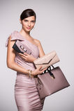 Fashion shopping purses. Beautiful glamour woman with jewellery posing with clutch and bag in elegant dress. Fashion girl deciding between clutch bag and purse Royalty Free Stock Photos