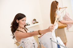 Fashion shopping - Two woman choose sale clothes royalty free stock photo