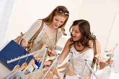 Fashion shopping - Two woman choose sale clothes Royalty Free Stock Image