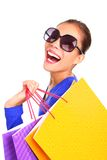 Fashion shopping woman happy with bags. Woman laughing while shopping. Excited girl walking looking back with her shopping bags on her shoulders. Isolated on Royalty Free Stock Photos