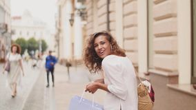 Fashion shopping woman open a package with purchases, while walking down the street of the city. shopping, shopping time.  stock video footage
