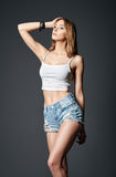 Fashion shot: beautiful girl in denim shorts and shirt Royalty Free Stock Image