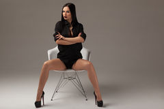 Fashion shot of a beautiful sexy brunette woman with long straight hair, black shirt and black shoes sitting on the chair Royalty Free Stock Photo