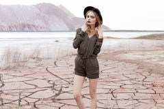 Fashion shot of a beautiful sexy girl in a black hat is removed in the desert for the magazine Royalty Free Stock Photo