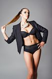 Fashion shot of beautiful young girl wearing black jacket, bra and pearl necklace Royalty Free Stock Image