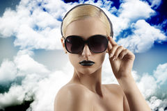 Fashion shot of blond girl with sunglasses looking Royalty Free Stock Image
