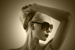 Fashion shot of blond girl with sunglasses posing Royalty Free Stock Photos