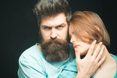 Fashion shot of couple after haircut. Hairstyle concept. Woman on mysterious face with bearded man, black background stock photo