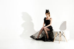 Fashion shot of elegant sad woman in black dress and veil sits on chair and waiting on white background Stock Photos