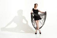 Fashion shot of elegant and sexy young woman in black dress and veil on white background Stock Photos