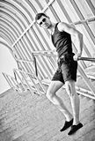 Fashion shot: handsome young man stands on staircase. Black and white Stock Photography