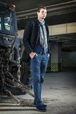 Fashion shot: handsome young man wearing jeans and coat against the tractor Stock Photo
