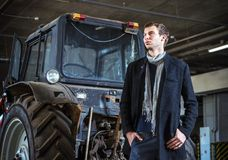 Fashion shot: handsome young man wearing jeans and coat against the tractor Stock Photography