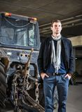 Fashion shot: handsome young man wearing jeans and coat against the tractor Stock Images