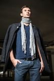Fashion shot: handsome young man wearing jeans, coat, shirt and scarf. Fashion shot: a handsome young man wearing jeans, coat, shirt and scarf Stock Images