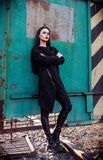 Fashion shot: portrait of cute rock girl informal model in tunic and leather pants standing in industrial area Stock Image