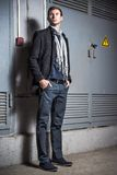 Fashion shot: portrait of handsome young man wearing jeans and coat Royalty Free Stock Image