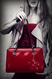Fashion shot of red patent leather bag. In woman hands Stock Photos