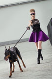 Fashion shot of a woman with black dog Stock Images