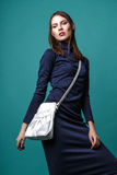 Fashion shot of a woman in blue drees with white bag in studio on green background Royalty Free Stock Photos