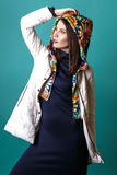 Fashion shot of a woman in white coat, blue drees in studio on green background Royalty Free Stock Image