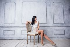 Fashion shot of young beautiful woman in white short dress sitting in antique chair. Fashion shot of young beautiful woman in white short dress sitting in Royalty Free Stock Photography