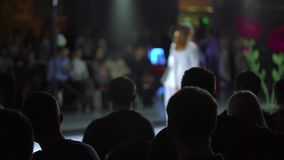 Fashion show. fashion podium, female model women girls in stylish dresses of designer walking on runway before audience. Viewers at defile show. Fashion catwalk stock footage