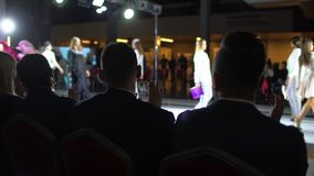 Fashion show. fashion podium, female model women girls in stylish dresses of designer walking on runway before audience. Viewers at defile show. Fashion catwalk stock video footage