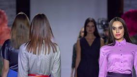Fashion show. fashion podium, female top model women girls in stylish dresses of designer walking on runway at defile