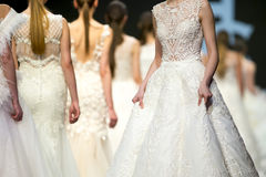 Fashion show runway beautiful wedding dresses. Female models walk the runway in beautiful stylish white wedding dresses during a Fashion Show. Fashion catwalk stock photography