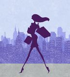 Fashion Silhouette of a Chic Young Woman Walking With Shopping B. Fashion silhouette of a chic young shopper with a city skyline in the background Stock Photo
