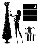 Fashion Silhouette of a Young Woman Decorating a Christmas Tree Royalty Free Stock Image