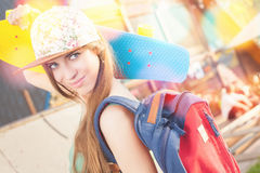 Fashion skateboarder young woman with a skateboard. Adventure, summer trip. Sport. Girl dressed in cap, wearing backpack. Accessories Stock Image