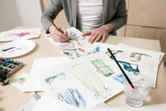 Fashion sketches on designer desk. With unrecognizable man in the background stock photography