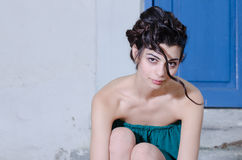 Fashion slim woman wearing green strapless short dress bending front Royalty Free Stock Photography