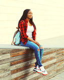Fashion smiling african woman wearing a red checkered shirt and backpack resting in the city. Park Royalty Free Stock Photography