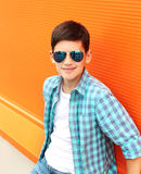 Fashion smiling child boy wearing a sunglasses and shirt. In city royalty free stock photography