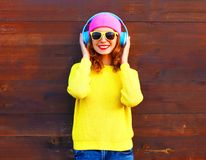 Fashion smiling girl listens to music in headphones, colorful pi. Nk hat yellow knitted sweater over wooden background Stock Images