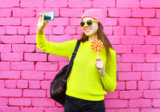 Fashion smiling girl taking photo selfie portrait using smartphone over colorful. Pink background Royalty Free Stock Image