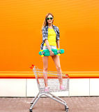 Fashion smiling hipster woman having fun with skateboard. Fashion smiling hipster woman having fun wearing a sunglasses and colorful clothes with skateboard Royalty Free Stock Photography