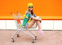 Fashion smiling hipster woman having fun wearing a sunglasses. With skateboard sitting in the shopping trolley cart outdoors Stock Image
