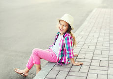 Fashion smiling little girl child wearing a checkered pink shirt and hat Stock Photo