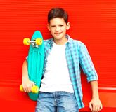 Fashion smiling teenager boy with skateboard in a checkered shirt stock photos